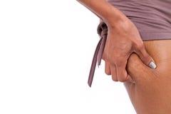 La mano della donna che giudica l'eccessivo grasso o celluliti della gamba, isolate immagini stock libere da diritti