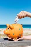 La mano della donna che inserisce euro nota nel porcellino salvadanaio alla spiaggia Immagine Stock