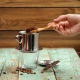 La mano della donna che mette caffè macinato in filtro francese dal metallo del gocciolamento fotografia stock libera da diritti