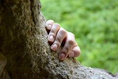 La mano della donna che tiene un bordo di pietra contro il verde Passaggio segreto immagini stock libere da diritti