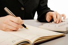 La mano della donna che tiene una scrittura della penna Fotografia Stock