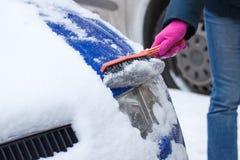La mano della donna che usando la spazzola e rimuove la neve dall'automobile e dal faro Fotografia Stock