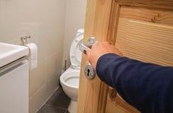 La mano della donna con il maglione blu scuro apre la maniglia di porta della toilette fotografie stock libere da diritti