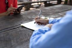 La mano della donna con la penna che completa il modulo di domanda Immagini Stock Libere da Diritti