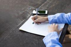La mano della donna con la penna che completa il modulo di domanda Fotografie Stock