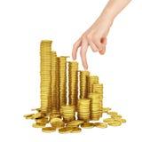 La mano della donna con le monete di oro su bianco Immagini Stock