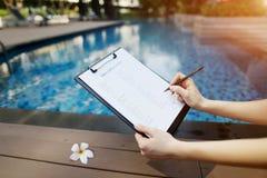 La mano della donna con la penna compila il modulo di domanda di visto in U.S.A. contro il fondo dello stagno Parte anteriore usa Immagine Stock