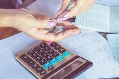la mano della donna di affari che calcola le sue spese mensili durante la tassa condisce con le monete, calcolatore Immagini Stock Libere da Diritti