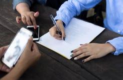 La mano della donna di affari con la penna che completa il modulo di domanda Immagini Stock Libere da Diritti