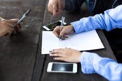 La mano della donna di affari con la penna che completa il modulo di domanda Immagini Stock