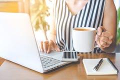 La mano della donna di affari tiene una tazza di caffè e sta lavorando ad un rivestimento Fotografia Stock