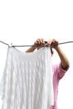 La mano della donna di lavoro domestico che appende la lavanderia bagnata pulita per asciugare i vestiti è Immagine Stock