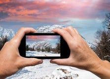 La mano della donna e dell'uomo che cattura l'inverno di Alpin abbellisce con smartph Immagine Stock