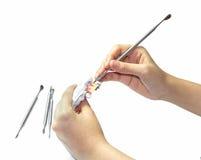 La mano della donna fa la protesi dentaria con lo strumento Immagini Stock Libere da Diritti