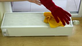 La mano della donna ha messo la sciarpa gialla ed i guanti rossi sul radiatore a casa archivi video