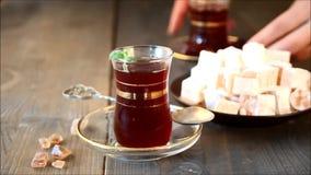 La mano della donna mette il tè turco in tazza di vetro tradizionale sulla tavola di legno orientale video d archivio