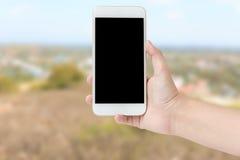 La mano della donna mostra lo smartphone mobile nella posizione verticale, offuscamento Fotografie Stock