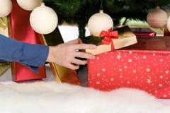 La mano della donna sta dando il regalo sotto l'albero di Natale Fotografie Stock