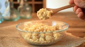 La mano della donna sta versando i grani cucinati della quinoa con il mestolo sul tavolo da cucina di legno stock footage