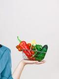 La mano della donna tiene il cestino della spesa con le verdure Fotografia Stock