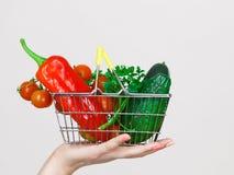 La mano della donna tiene il cestino della spesa con le verdure Fotografia Stock Libera da Diritti
