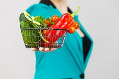 La mano della donna tiene il cestino della spesa con le verdure Fotografie Stock