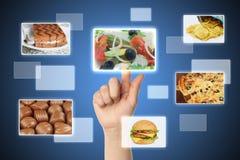 La mano della donna usa l'interfaccia dello schermo di tocco con alimento Fotografia Stock Libera da Diritti