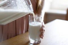 La mano della donna versa il latte in un vetro da un decantatore immagini stock
