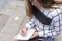 La mano della giovane donna con la penna scrive il taccuino bianco nella via Immagini Stock