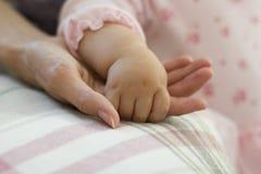 La mano della madre della tenuta del bambino Immagini Stock