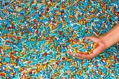 La mano della manifestazione dell'uomo molte medicine variopinte espira sul pavimento del cemento Fotografia Stock