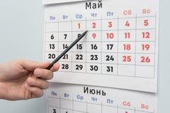 La mano della matita indica i fine settimana e le feste lunghi su un calendario murale fotografia stock libera da diritti