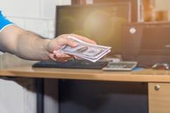 La mano della persona accetta il dono dei soldi dal progetto di costruzione, corrotto Fotografie Stock