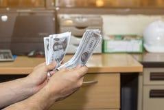 La mano della persona accetta il dono dei soldi dal progetto di costruzione, corrotto Immagini Stock