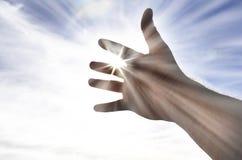 La mano della persona che raggiunge verso la luce solare di cielo Immagini Stock Libere da Diritti