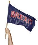 La mano della persona che tiene una bandiera d'ondeggiamento con la parola Brexit, rappresentazione 3D Fotografia Stock Libera da Diritti
