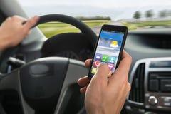 La mano della persona facendo uso del cellulare mentre conducendo un'automobile Fotografie Stock Libere da Diritti