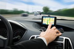 La mano della persona facendo uso del sistema di navigazione dei gps in automobile Fotografia Stock
