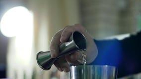 La mano della persona tiene il jigger e lento versa il cognac nell'agitatore su un fondo unfocused video d archivio