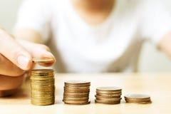 La mano della pila mettente maschio della moneta di oro aumenta la crescita, i finanziaria Fotografie Stock