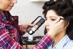 La mano della pittura del padrone di trucco, compone in corso Il truccatore si applica la mascara ai cigli della ragazza di model fotografie stock libere da diritti