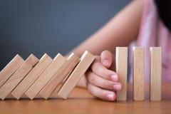 La mano della ragazza che ferma effetto di domino di legno di caduta rovesciato da continuo o dal rischio immagine stock libera da diritti