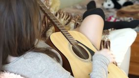 La mano della ragazza colpisce le corde della chitarra video d archivio