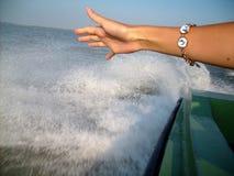 La mano della ragazza contro lo sfondo della spruzzatura dell'acqua fotografie stock libere da diritti