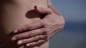 La mano della ragazza ha messo una crema protettiva dello spruzzo sul suo stomaco video d archivio