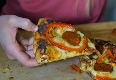 La mano della ragazza tiene una fetta di pizza fotografia stock libera da diritti