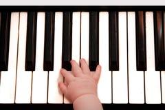 La mano della tastiera di piano e del piccolo bambino Immagine Stock Libera da Diritti