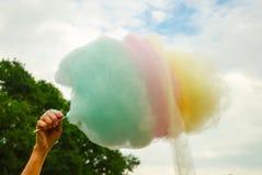 La mano delle donne che tengono zucchero filato colorato nel backgrou fotografie stock libere da diritti