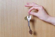 La mano delle donne che tiene due chiavi dall'appartamento Immagine Stock Libera da Diritti