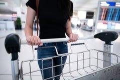 La mano delle donne del primo piano sta spingendo il carrello con le valigie al Fotografia Stock Libera da Diritti